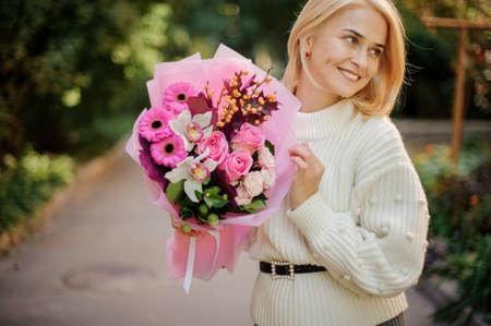woman holds beautiful bouquet with pink flowers in her hands and looks away. 免版税图像