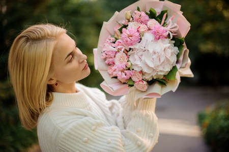 young woman holds delicate bouquet of pastel pink colors and looks at it