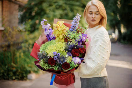 young blonde woman in white sweater holds bouquet with different bright flowers 免版税图像