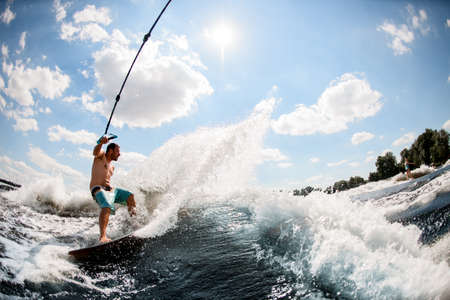 athletic man wakesurfing on the river and pulled by a boat.