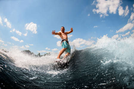 emotional adult guy actively ride on the waves on surfboard against blue sky
