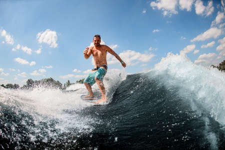 athletic guy actively ride on the waves on surfboard against blue sky