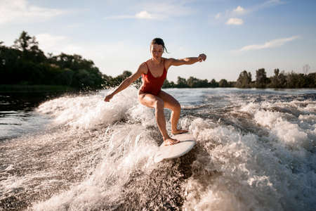 handsome woman rides down on surfboard on river wave from boat