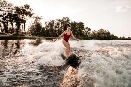 front view of woman who riding surfboard on wave. Stock fotó