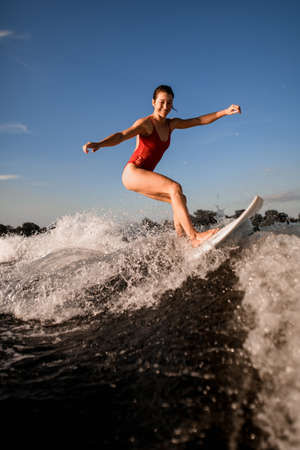 Smiling female wakesurfer in red swimsuit rides up the wave on surfboard
