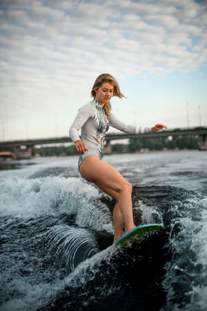 blonde woman masterfully rides down the wave on surfboard against cloudy sky background 写真素材