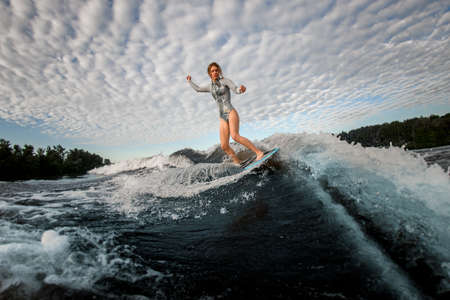 view of young woman who standing on wakesurf board and riding the wave Imagens
