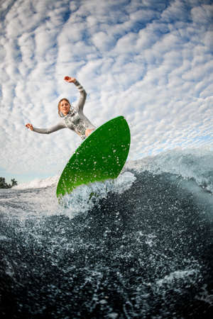 beautiful blonde woman actively rides on a surfboard on the wave