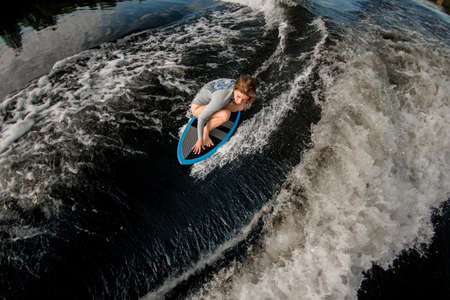 top view of woman who rides down the wave on surfboard