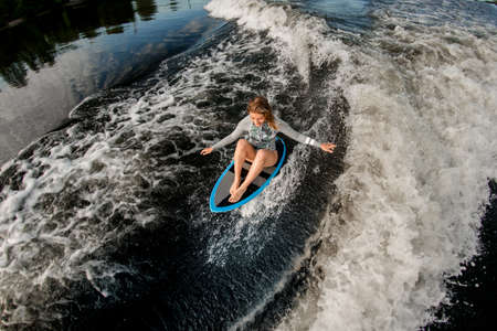 top view of blond woman who riding the waves while sitting on wakesurf board