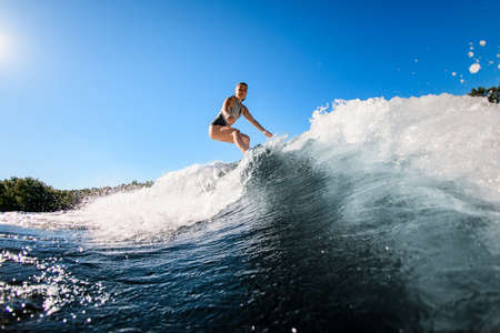 active young woman masterfully rides the wave on surfboard