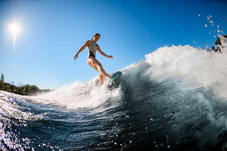 active young wet woman masterfully rides the wave on surfboard 스톡 콘텐츠