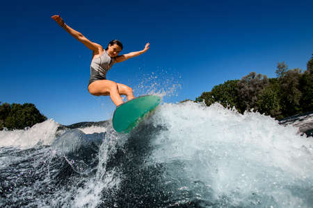 happy woman wakesurfer in gray swimsuit jumps with bright surf board