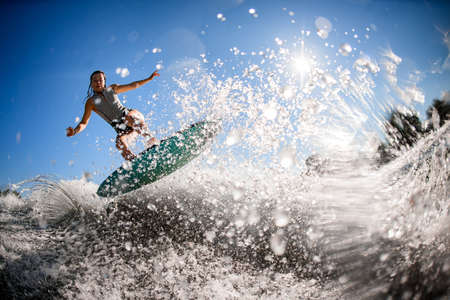 gorgeous view of athlete woman in gray swimsuit who jumps with bright surf board. 写真素材