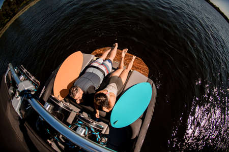 top view of man and woman lying on motor boat and surfboards nearby
