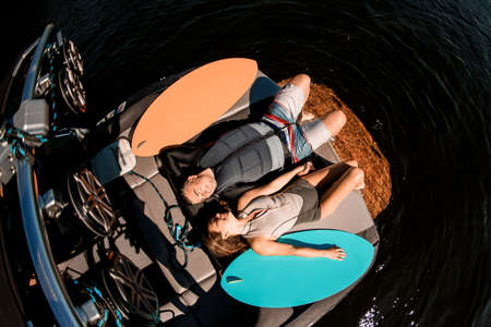 top view of happy man and woman lying on motor boat and surfboards nearby Banque d'images