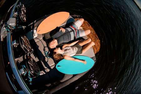 top view of man and woman lying on motor boat and looking at each other Banque d'images