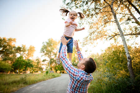 little funny girl being thrown up in the air by her father Stockfoto