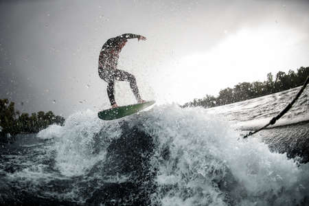 brave man rides on splashed wave off the coast with his surfboard.
