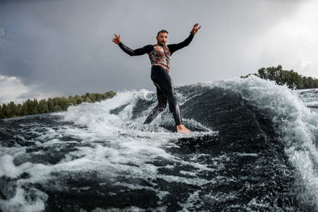 attractive man having fun rides wave on surfboard in the summer day