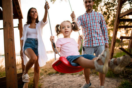 cheerful young father and mother swing their cute little daughter on swing