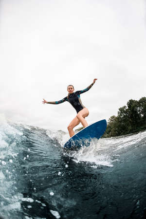 Active woman stands with bent knees on surfboard and ride on wave