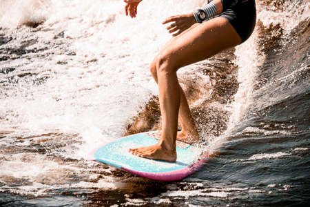 close-up of athletic legs of young woman riding wave on surf style wakeboard