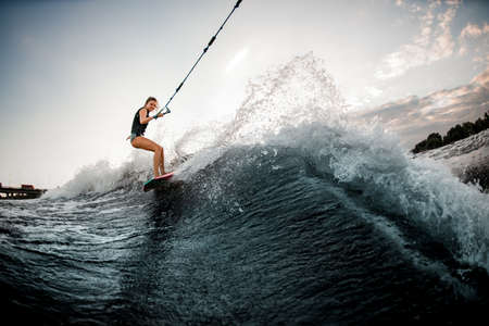 view of young woman on surf style wakeboard who holds on to rope and rides on wave from boat