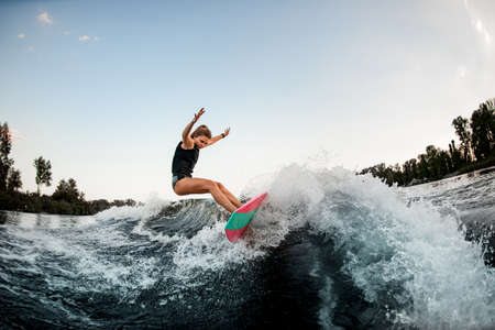 handsome woman balanced on surf style wakeboard on splashed river wave