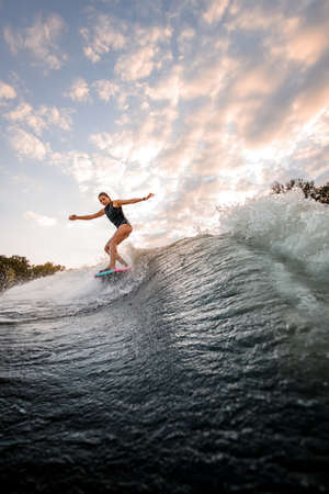 handsome woman rides down on surf style wakeboard on splashed river wave