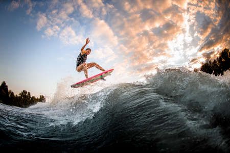 athletic woman skillfully jumping over big splashing wave on surf style wakeboard.