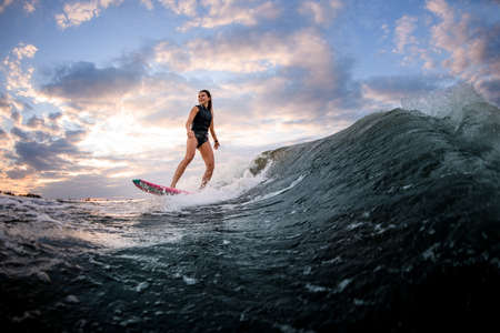 Young smiling woman riding down the wave on bright surf style wakeboard. Imagens