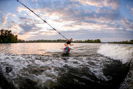 view of smiling woman riding on surf style wakeboard and holding tight rope
