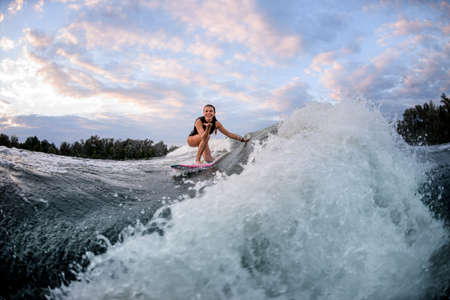Active woman rides wave on surf style wakeboard and touches wave with hand