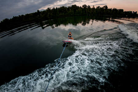 high angle view of woman on surf style wakeboard holding rope and rides on water