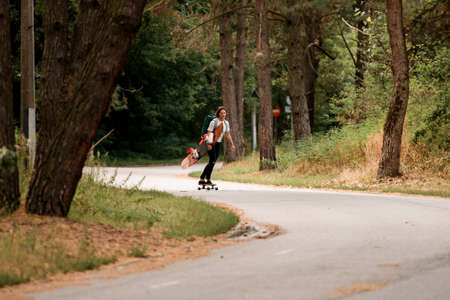 view of road along which young woman rides on skateboard with wakeboard in her hand