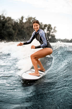 Cheerful young woman in black swimsuit rides down the wave on surfboard.