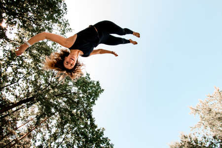 Smiling young woman jumping and tumbling in the air against the blue sky. 版權商用圖片