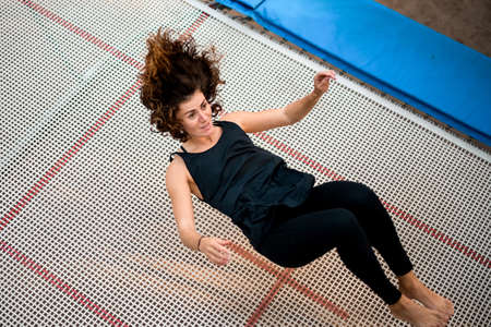 young athletic woman jumping while lying on large trampoline