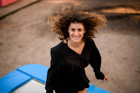 high angle view of young cheerful woman jumping on trampoline.