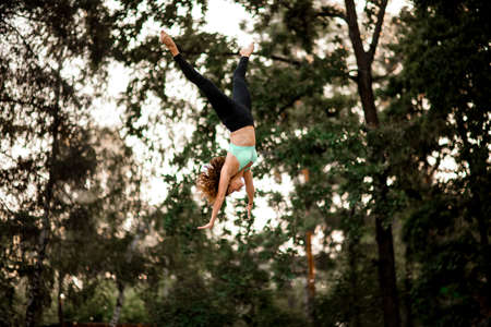 attractive woman jumping masterfully and performs trick upside down in the air Фото со стока
