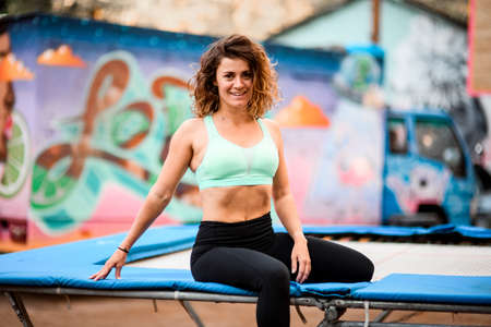 view on woman with curly hair in bright sports top sitting on trampoline