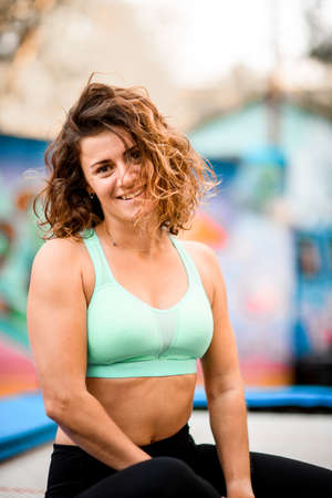 view on attractive woman with curly hair in bright sports top