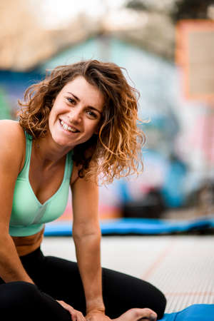view on beautiful woman with curly hair in bright sports top