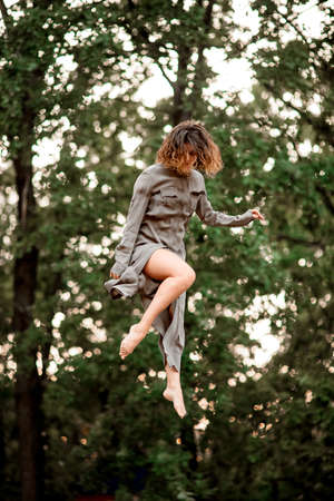 young woman in long gray shirt jumps high into the air
