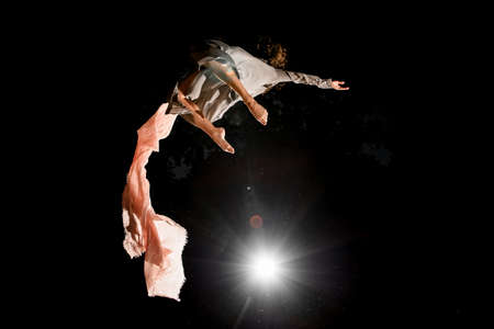 young woman beautifully jumps in the air at night
