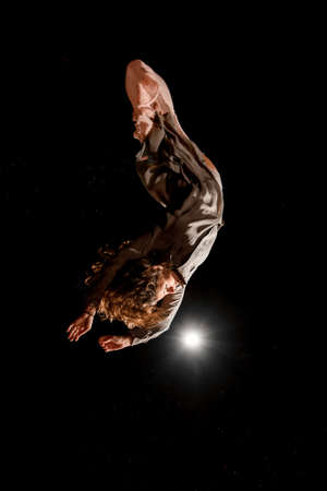 beautiful woman jumps and performs trick upside down in the air at dark time