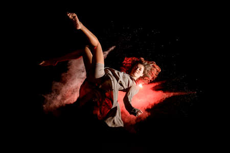smiling woman bouncing in the air and performs trick at dark time