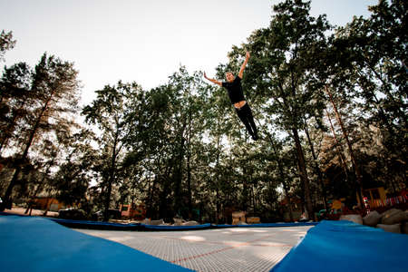 Athletic man jumps on trampoline against the backdrop of green trees and sky.