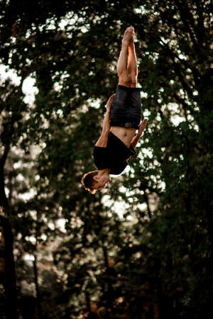 man jumps and performs trick upside down in the air 版權商用圖片